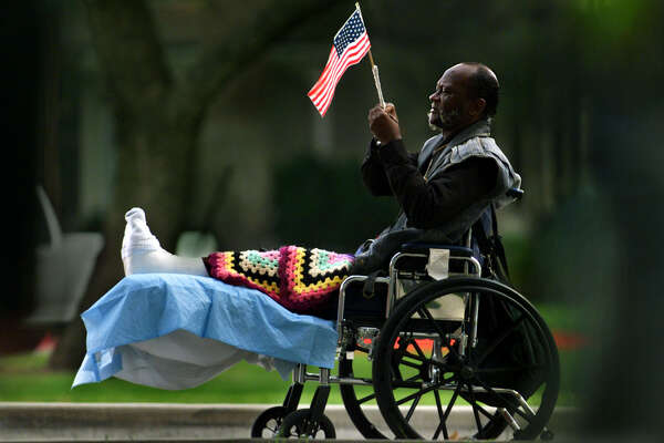 Before the Veteran's parade held at the West L.A. Veteran's hospital, veteran Bryant Harris puts a flag on his wheelchair. He spent 16 years in the military serving both in the Navy and Army starting back in 1964, as an Army medic and a Navy corpsman. He continues to serve his country now as a staff nurse at the West Los Angeles Veterans hospital, where he is recovering from an accident.  (Photo by Carolyn Cole/Los Angeles Times via Getty Images)