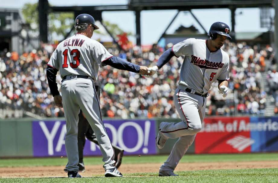 Minnesota Twins' Eduardo Escobar, right, shakes hands with third base coach Gene Glynn (13) after hitting a solo home run against the San Francisco Giants during the second inning of a baseball game on June 11, 2017 in San Francisco. Photo: AP Photo — Marcio Jose Sanchez  / Copyright 2017 The Associated Press. All rights reserved.