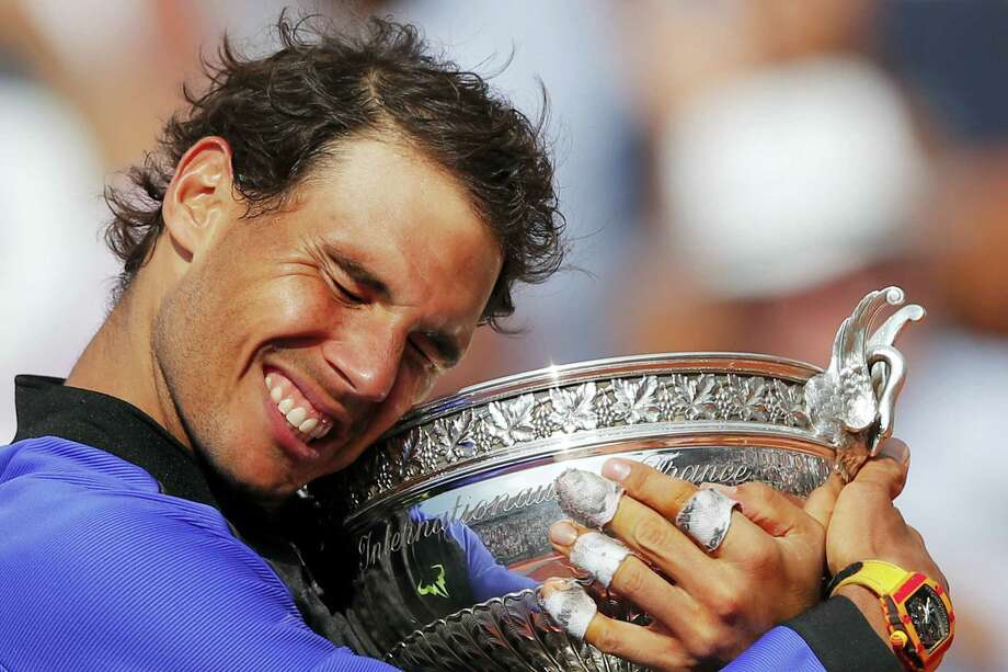 Spain's Rafael Nadal holds the trophy as he celebrates winning his tenth French Open title against Switzerland's Stan Wawrinka in three sets, 6-2, 6-3, 6-1, during their men's final match of the French Open tennis tournament at the Roland Garros stadium in Paris, France on Sunday, June 11, 2017. Photo: AP Photo — Christophe Ena  / Copyright 2017 The Associated Press. All rights reserved.