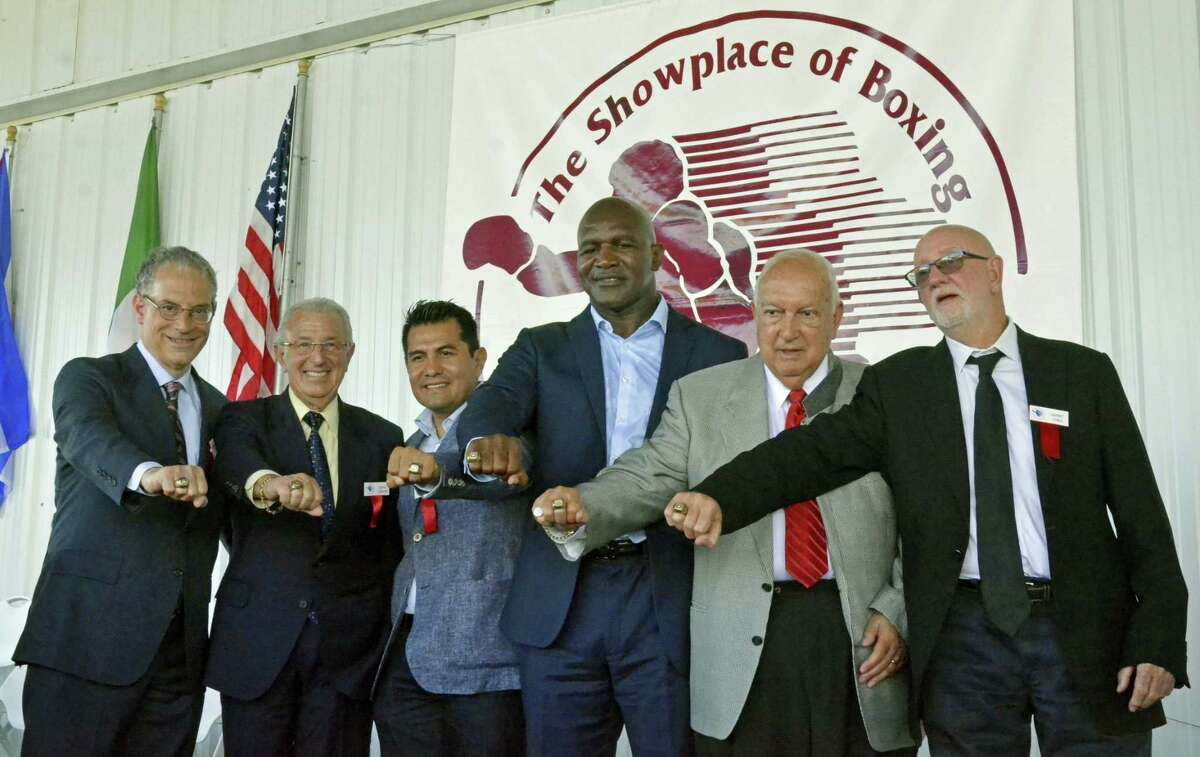 International Boxing Hall of Fame Class of 2017 inductees, from left, Steve Farhood, Barry Tompkins, Marco Antonio Barrera, Evander Holyfield, Jerry Roth and Johnny Lewis display their rings following the induction ceremony in Canastota, N.Y., Sunday.