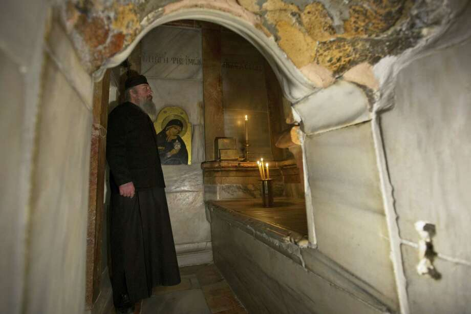 A Greek priest stands inside the renovated Edicule in the Church of the Holy Sepulchre, traditionally believed to be the site of the crucifixion of Jesus Christ, in Jerusalem's old city Monday, Mar. 20, 2017. A Greek restoration team has completed a historic renovation of the Edicule, the shrine that tradition says houses the cave where Jesus was buried and rose to heaven. Photo: AP Photo — Sebastian Scheiner  / Copyright 2017 The Associated Press. All rights reserved.