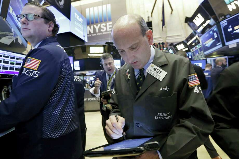 Trader Andrew Silverman, right, works on the floor of the New York Stock Exchange Wednesday. Photo: Richard Drew — The Associated Press  / AP