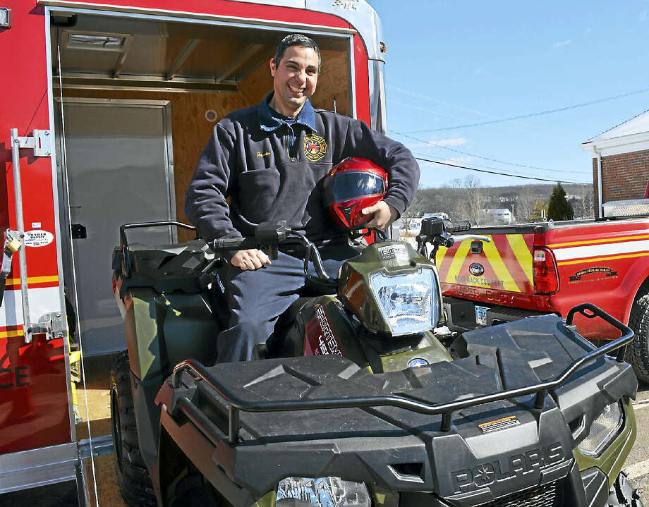 South Fire District Firefighter James Mastroianni demonstrates the department's new Polaris Sportsman all-terrain vehicle at the Middletown station. Photo: Cassandra Day — The Middletown Press