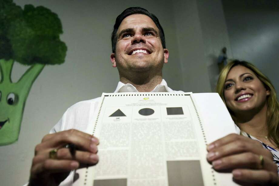 Gov. Ricardo Rossello shows his ballot at the San Jose Academy during the fifth referendum in San Juan, Puerto Rico, Sunday, June 11, 2017. Puerto Ricans are getting the chance to tell U.S. Congress on Sunday which political status they believe best benefits the U.S. territory as it remains mired in a deep economic crisis that has triggered an exodus of islanders to the U.S mainland. Congress ultimately has to approve the outcome of Sunday's referendum that offers voters three choices: statehood, free association/independence or current territorial status. (AP Photo/Carlos Giusti) Photo: AP / Copyright 2017 The Associated Press. All rights reserved.