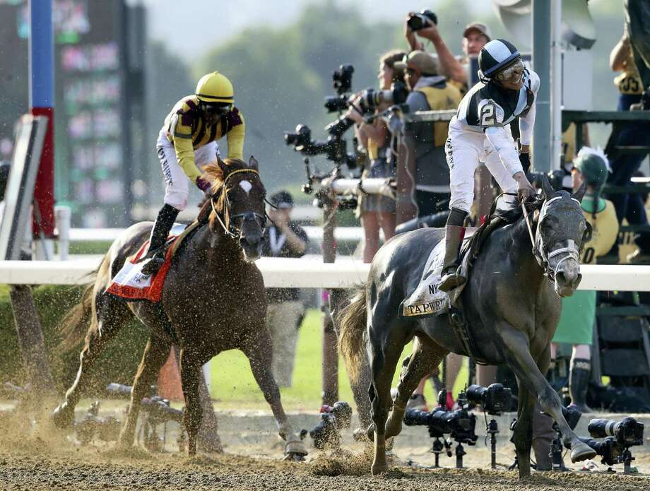 Jose Ortiz celebrates after riding Tapwrit to victory in the 149th running of the Belmont Stakes Saturday in Elmont, N.Y. Irish War Cry, ridden by Rajiv Maragh, is at left. Photo: Mary Altaffer — The Associated Press  / Copyright 2017 The Associated Press. All rights reserved.