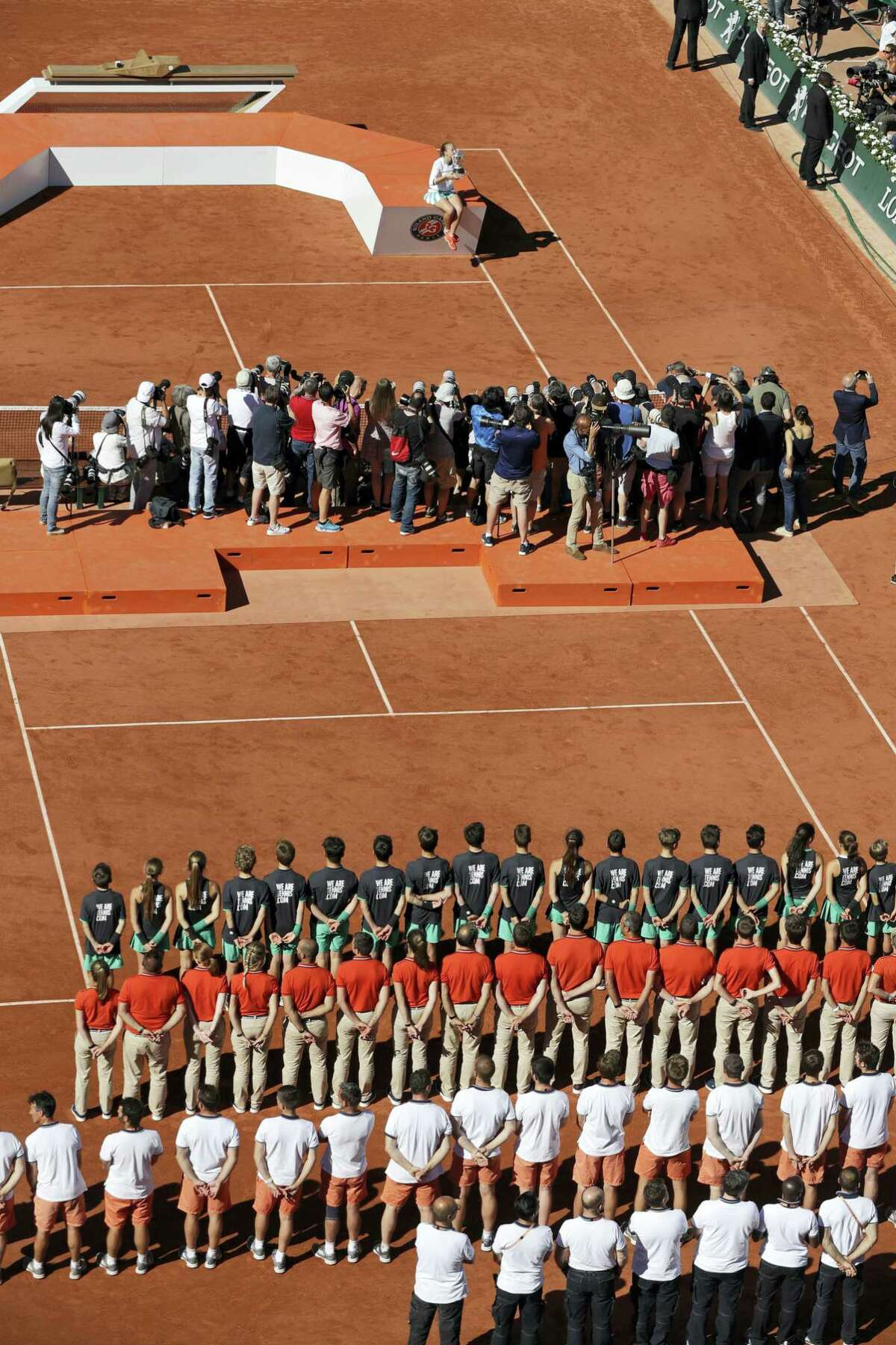 Latvia's Jelena Ostapenko, top, kisses the trophy during the award ceremony after winning the women's final match of the French Open tennis tournament against Romania's Simona Halep in three sets 4-6, 6-4, 6-3, at the Roland Garros stadium, in Paris, France, Saturday, June 10, 2017.