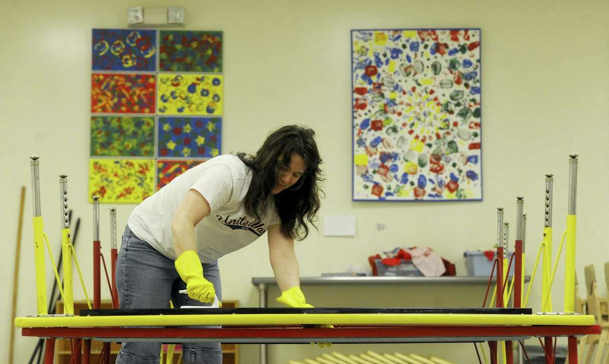 A woman cleans classroom tables as part of the 2015 United Way Day of Action.