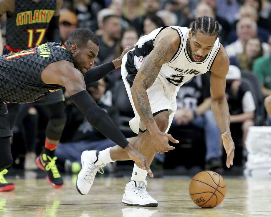 Atlanta Hawks forward Paul Millsap (4) knocks the ball away from San Antonio Spurs forward Kawhi Leonard (2) during the second half of an NBA basketball game on Monday, March 13, 2017 in San Antonio. Spurs won 107-99. Photo: AP Photo — Eric Gay  / Copyright 2017 The Associated Press. All rights reserved.