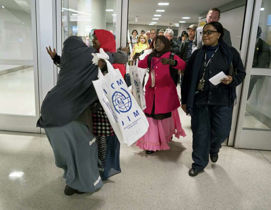 Halima Mohamed, embraces her daughter Muzamil Shalle, 14, left, as her other daughter Miski Shalle, 11, center, approaches, she sees her children for the first time in seven years at John F. Kennedy International Airport in New York on March 8, 2017. The parents, who are from Somalia, but have been living in Mechanicsburg, Pa., were originally scheduled to receive the children earlier this year, but the process was delayed due to a security check expiring as a result of delayed travel caused by the Jan. 27, 2017 White House travel ban executive order. Photo: AP Photo — Craig Ruttle  / FR61802 AP
