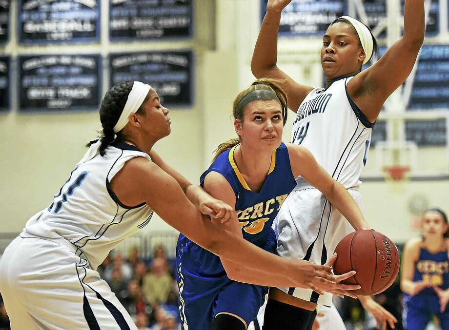 Mercy's Samantha Chapps, center, eyes the hoop while driving between Middletown's Dominique Highsmith, left, and Brielle Wilborn during Thursday's Class LL quarterfinal game on Thursday at the LaBella-Sullivan Gymnasium at Middletown High. Photo: Catherine Avalone — New Haven Register  / Catherine Avalone/New Haven Register