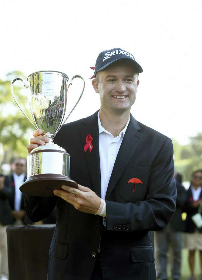 Russell Knox holds the trophy after winning the Travelers Championship golf tournament last August in Cromwell. Photo: ASSOCIATED PRESS FILE PHOTO  / FR153656 AP