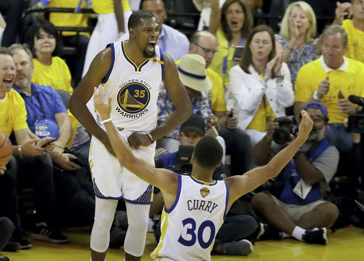 Golden State Warriors forward Kevin Durant (35) celebrates with guard Stephen Curry (30) during the second half of Game 2 of basketball's NBA Finals against the Cleveland Cavaliers in Oakland, Calif. on June 4, 2017.