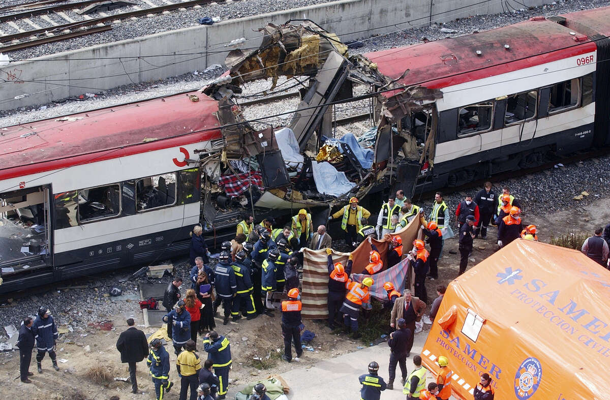 FILE - In this March 11, 2004 file photo, rescue workers cover up bodies alongside a bomb-damaged passenger train, following a number of explosions in Madrid, Spain, killing 191 people and wounding more than 500 in Spain's worst terrorist attack ever. The deadly vehicle and knife attack Saturday, June 3, 2017, on London Bridge and in nearby Borough Market is the latest attack in Europe in recent years. (AP Photo/Paul White, File)