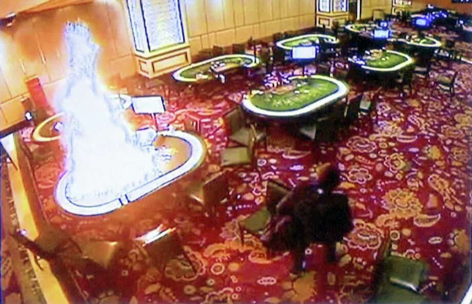 In this image made from security video released by Manila Police and Resorts World Manila on Saturday, June 3, 2017, a gunman walks away after setting fire to a gambling table in the Resorts World Manila entertainment and gambling complex in suburban Pasay city, southeast of Manila, Philippines on Friday, June 2, 2017. Dozens were killed during the attack, mostly from smoke inhalation. Photo: AP Photo/Bullit Marquez   / Resorts World Manila