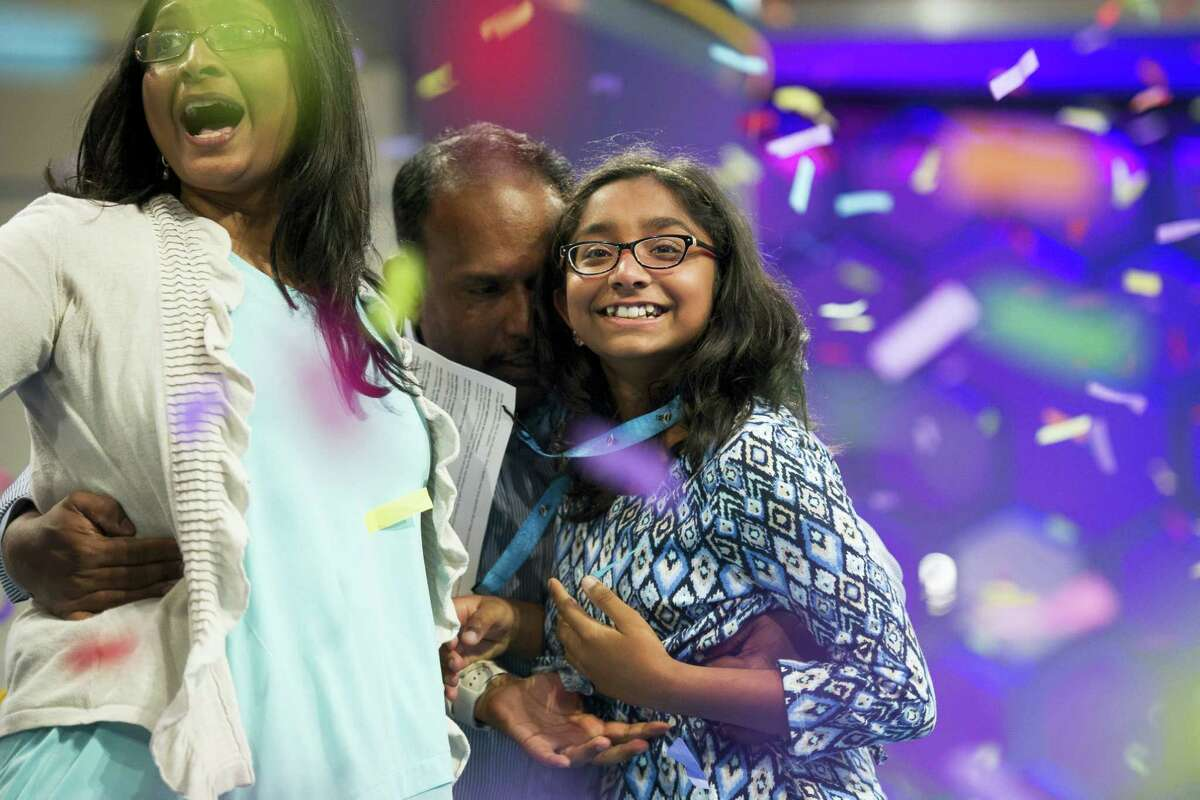 Ananya Vinay, 12, from Fresno, Calif., celebrates onstage with her parents, Anu Pama Poliyedathpp, left, and Vinay Sreekumar, center, after winning the 90th Scripps National Spelling Bee in Oxon Hill, Md., Thursday, June 1, 2017.