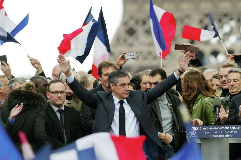 "French conservative presidential candidate Francois Fillon cheers the crowd after delivering his speech during a rally in Paris Sunday. Fillon is urging his supporters not to ""give up the fight"" for the presidency despite corruption allegations dogging him. Photo: AP Photo — Christophe Ena   / Copyright 2017 The Associated Press. All rights reserved."