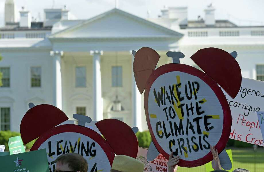 Protesters gather outside the White House in Washington, Thursday, to protest President Donald Trump's decision to withdraw the Unites States from the Paris climate change accord.  AP Photo — Susan Walsh Photo: AP / Copyright 2017 The Associated Press. All rights reserved.