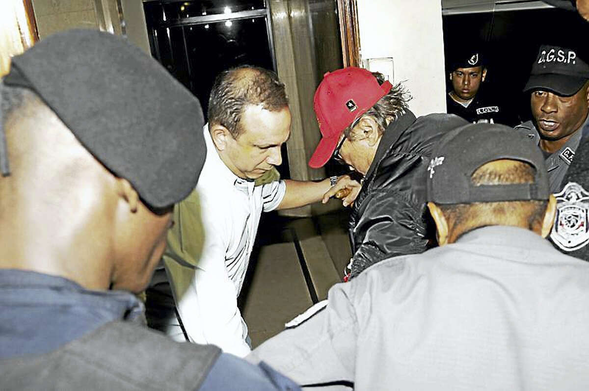 In this Jan. 28, 2017, file photo, Panamanian ex-dictator Manuel Antonio Noriega, wearing a red baseball cap, arrives after being placed under house arrest for three months in Panama City. Noriega has been hospitalized to undergo surgery to remove a benign tumor from his brain. Thays Noriega, one of his daughters, said surgery was scheduled for Tuesday, March 6.