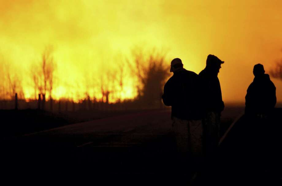 People are silhouetted against the orange glow of the fire as they watch a large grass fire burning out of control on Monday, March 6, 2017, in the northeast of Hutchinson, Kan. Photo: Lindsey Bauman/The Hutchinson News Via AP   / The Hutchinson News