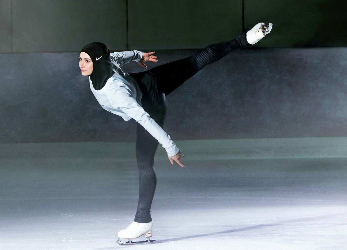 In this undated image provided by Nike, figure skater Zahra Lari model wears Nike's new hijab for Muslim female athletes. The pull-on hijab is made of light, stretchy fabric that includes tiny holes for breathability and an elongated back so it will not come untucked. It will come in three colors: black, vast grey and obsidian. Beaverton-based Nike says the hijab will be available for sale next year.