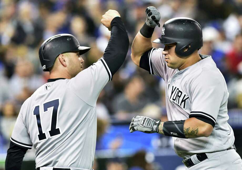 Matt Holliday, left, congratulates Gary Sanchez on his solo home run in the second inning Thursday. Photo: Frank Gunn — The Canadian Press Via AP  / The Canadian Press