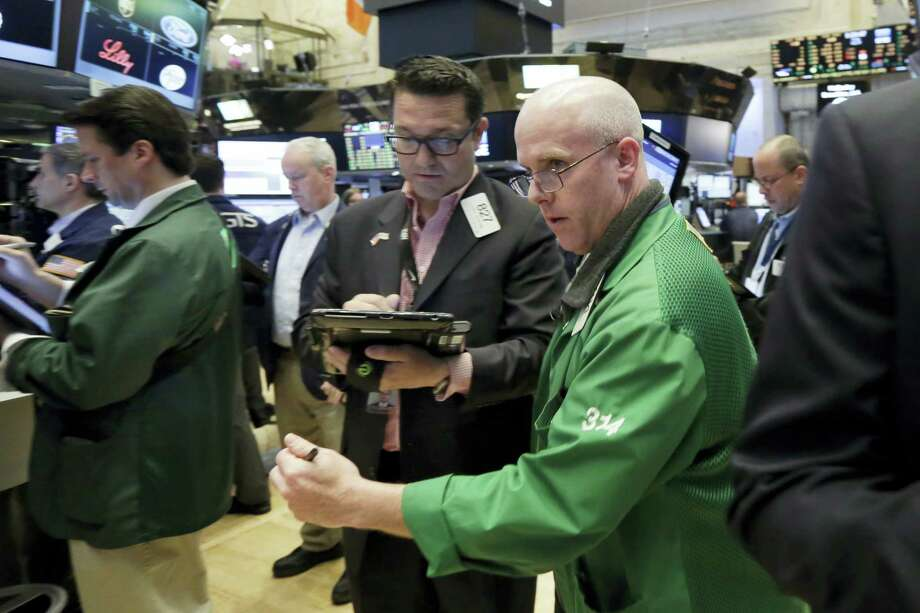 Kevin Walsh, right, moves between fellow traders as he works on the floor of the New York Stock Exchange. Photo: Richard Drew — The Associated Press File  / AP