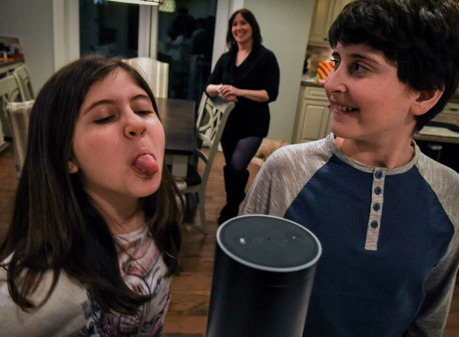 "Laura Labovich (background) and her children Asher (right), 13, and Emerson, 10, with the family ""Alexa"", an artificial intelligence device, on January, 29, 2017 in Bethesda, Md. Photo: Washington Post Photo — Bill O'Leary  / The Washington Post"