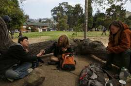 From left, Peaches, who has lived in the park for 12 years, Gnome and Erin smoke and hang out in People's Park August 11, 2017 in Berkeley, Calif.