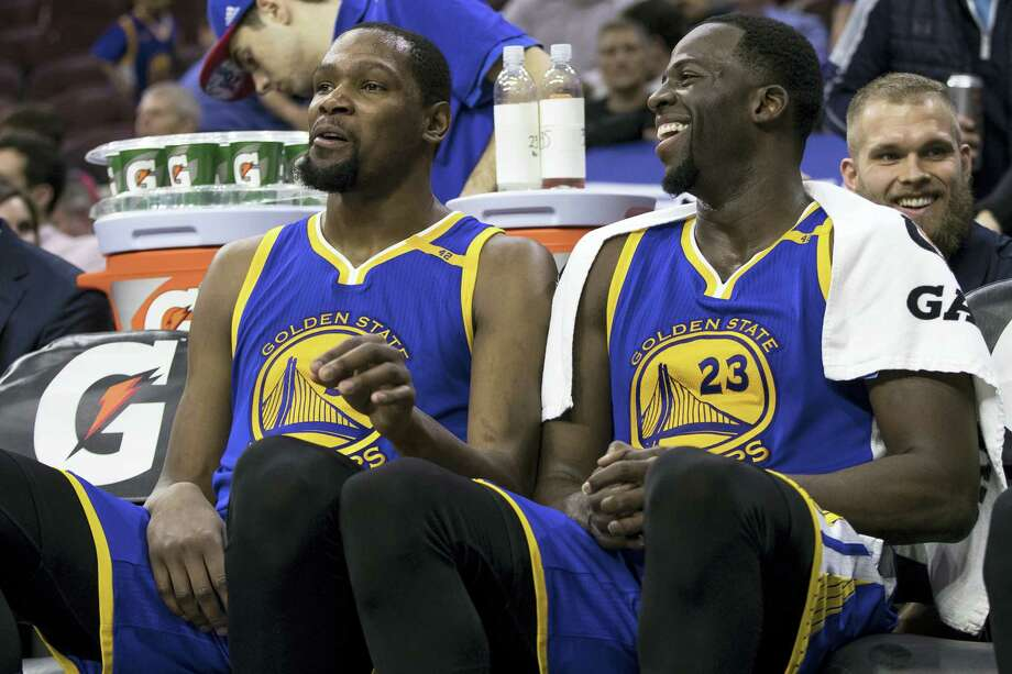 Golden State Warriors' Kevin Durant, left, looks on from the bench with Draymond Green, right, during the second half of an NBA basketball game against the Philadelphia 76ers on Feb. 27, 2017 in Philadelphia. The Warriors won 119-108. Photo: AP Photo — Chris Szagola  / FR170982 AP