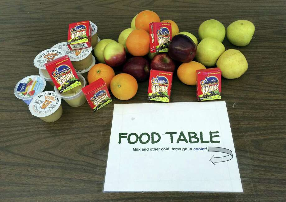 In this Tuesday, Feb. 28, 2017, photo, uneaten food that students have donated sits on a table where it can be shared with classmates at James H. Moran Middle School in Wallingford, Conn. School officials there are criticizing a state policy change that restricts sharing of some uneaten food items. Photo: AP Photo/Michael Melia   / Copyright 2017 The Associated Press. All rights reserved.