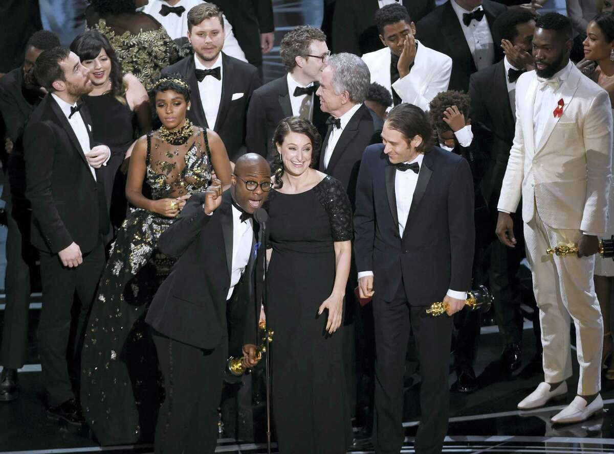 "Barry Jenkins, foreground left, and the cast accept the award for best picture for ""Moonlight"" at the Oscars on Feb. 26, 2017 at the Dolby Theatre in Los Angeles."
