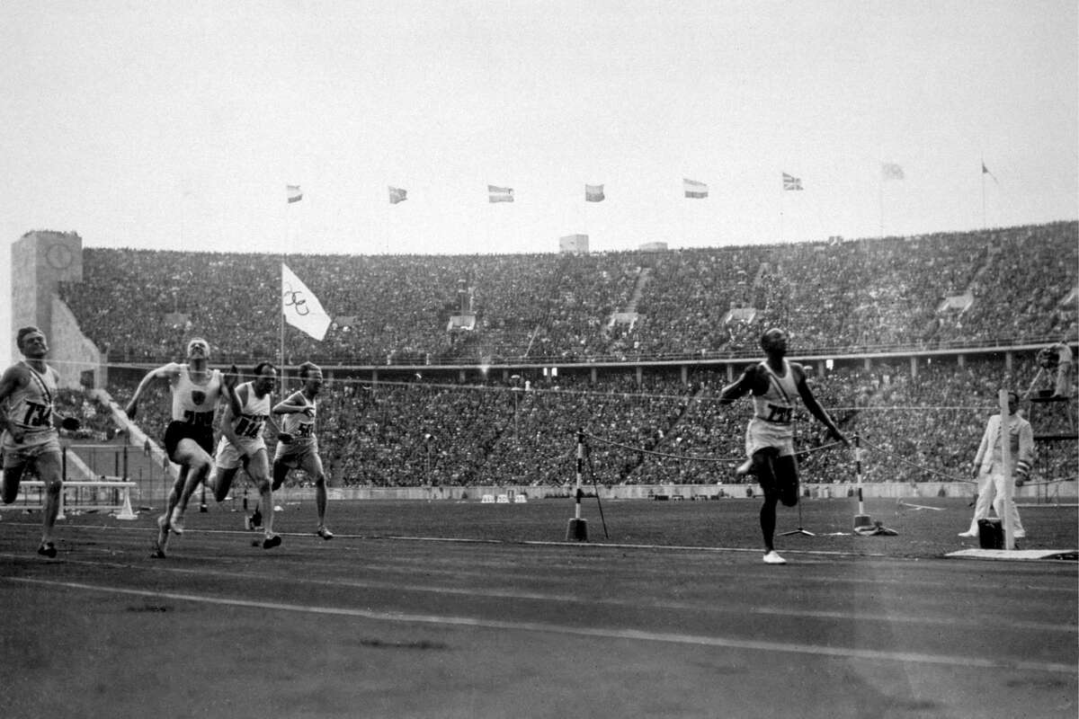 Nazi Germany Olympics Jesse Owens (1913 - 1980) of the USA (right) crosses the finishing line to win the 100 metres at the 1936 Olympics in Berlin. He won three other gold medals, in the 200 metres, 4 X 100 metres relay and long jump.