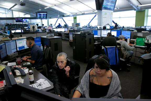 Dispatchers Justin Wong, (left) and  Joan Vallarino, (center) with  Kim Delara, a dispatch trainee at the San Francisco 911 Emergency Call Center on Mon. July 31, 2017 in San Francisco, Ca.
