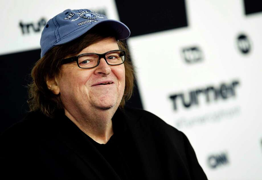 "FILE - In this May 17, 2017 file photo, filmmaker Michael Moore attends the Turner Network 2017 Upfront presentation at The Theater at Madison Square Garden in New York.    Moore showed his patriotism by marching down the Avenue of the Americas with a drum and fife corps after making his Broadway debut. ""I say this to the people who disagree with me, we're all Americans. We're all in the same boat, and we're going to sink or swim together. I prefer not to sink. So let's find a way, if we can, to work together to save this country,"" Moore said Thursday, Aug. 10.  .(Photo by Evan Agostini/Invision/AP, File) ORG XMIT: NY111 Photo: Evan Agostini / 2017 Invision"