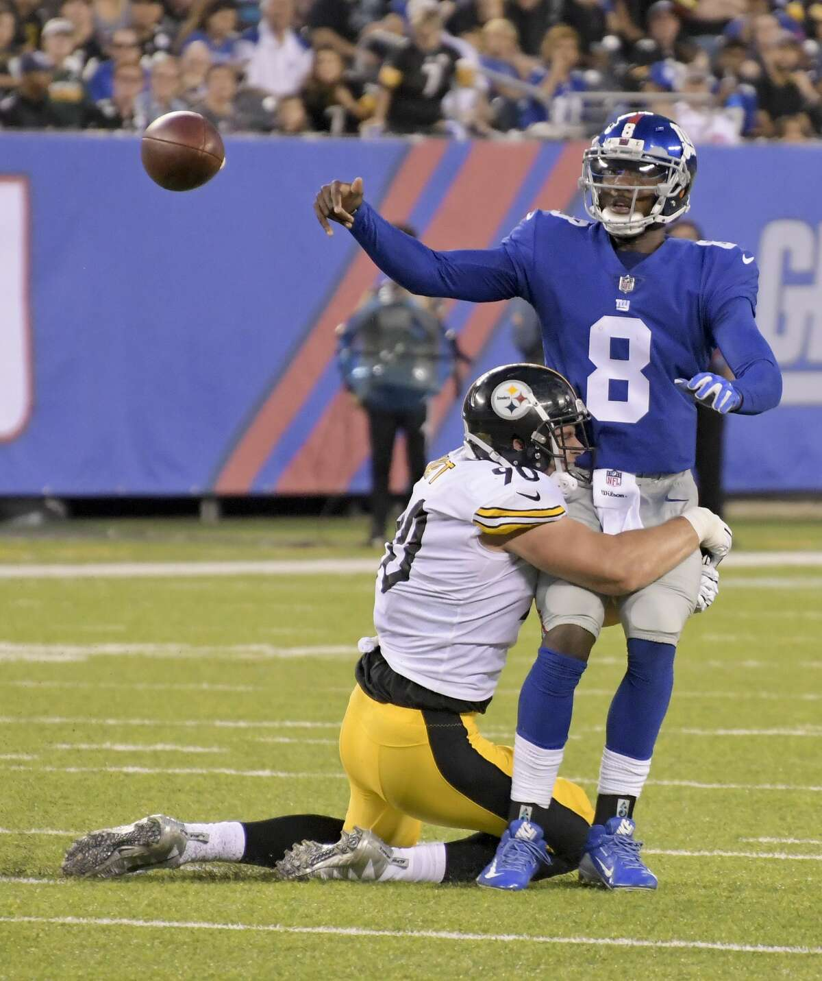New York Giants quarterback Josh Johnson (8) throws the ball as he is hit by Pittsburgh Steelers linebacker T.J. Watt (90) during the second quarter of a preseason NFL football game, Friday, Aug. 11, 2017, in East Rutherford, N.J. (AP Photo/Bill Kostroun)