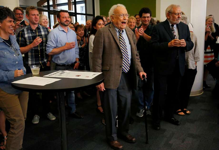 S.F. Chronicle Science Editor David Perlman (center), at his retirement party, walks to the front of the room full of colleagues, friends and dignitaries as he is announced by Editor in Chief Audrey Cooper. Photo: Leah Millis, The Chronicle