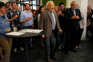 Former San Francisco Chronicle Science Editor David Perlman, 98, center, walks to the front of the room as he is announced by the Chronicle's Editor in Chief Audrey Cooper while surrounded by past and present colleagues at a party recognizing the decades of work Perlman has accomplished while working for the San Francisco Chronicle August 11, 2017 at the Chronicle's headquarters in San Francisco, Calif.