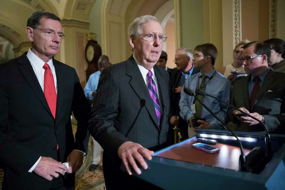 FILE- In this Aug. 1, 2017, photo, Senate Majority Leader Mitch McConnell, R-Ky., joined at left by Sen. John Barrasso, R-Wyo., holds his first news conference since the Republican health care bill collapsed last week due to opposition within the GOP ranks, on Capitol Hill, in Washington. People want President Donald Trump and congressional Republicans to try making the Obama health care law more effective, according to a national poll released Friday, Aug. 11, by the nonpartisan Kaiser Family Foundation. (AP Photo/J. Scott Applewhite, File) Photo: J. Scott Applewhite, STF / Copyright 2017 The Associated Press. All rights reserved.