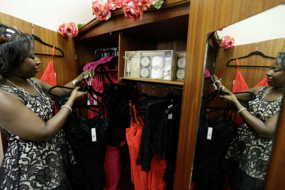 Psyche Terry, owner of Urban Intimated, arranges her products at the Indulge Your Senses boutique in Little Elm. Terry participated in The Workshop at Macy's training program. Texas is a leader in minority-owned businesses. Photo: LM Otero, STF / AP