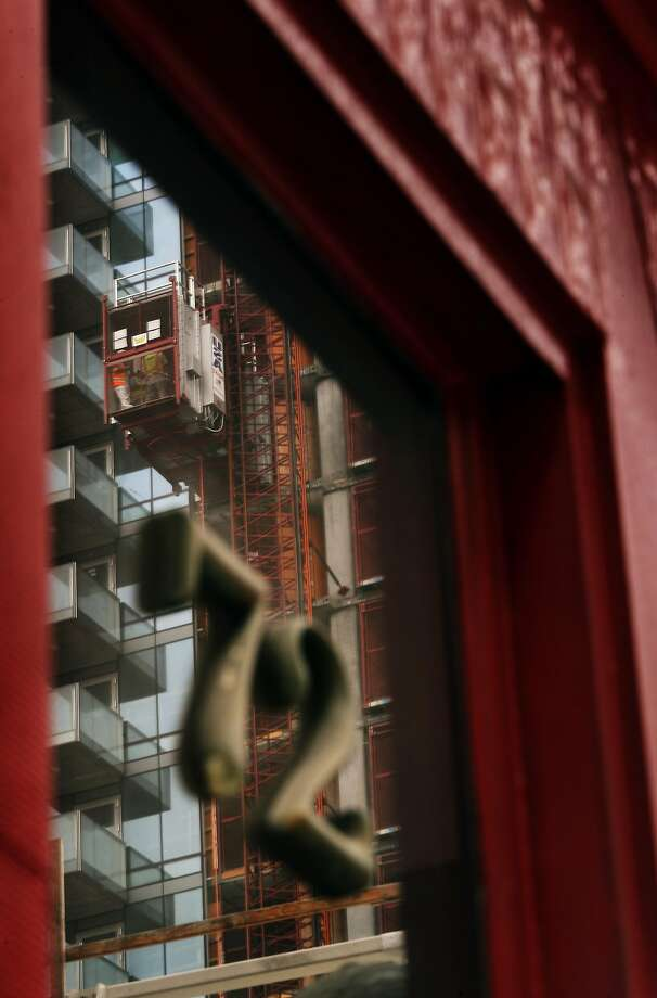 A construction elevator is seen reflected in the window of Brizart and Young Sheet Metal on Tehama Street in San Francisco, Calif., on Thursday, August 10, 2017. The block of Tehama Street between 1st and 2nd Streets exemplifies the changes taking place south of Market Street as technology and high rise housing moves into the area. Photo: Carlos Avila Gonzalez, The Chronicle