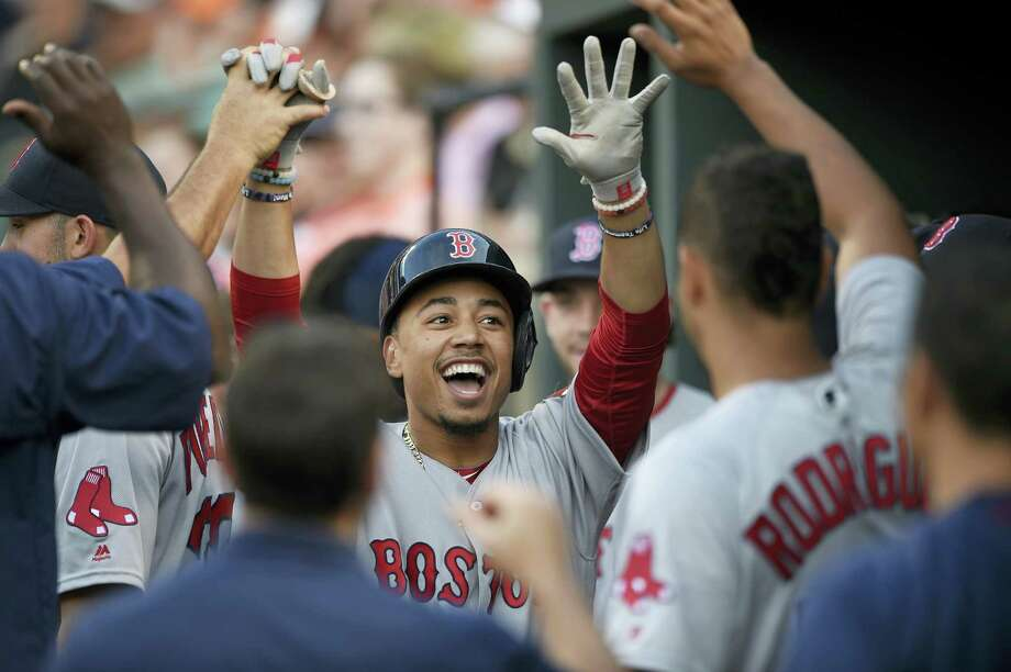 Boston Red Sox' Mookie Betts celebrates his home run in the dugout during the first inning against the Baltimore Orioles, Tuesday, May 31, 2016, in Baltimore. Betts homered three times in the 6-2 victory. Photo: NICK WASS — THE ASSOCIATED PRESS  / FR67404 AP