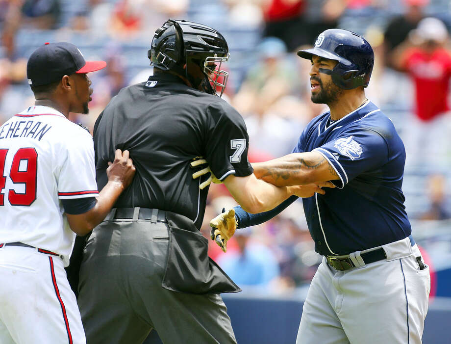 Home plate umpire Jordan Baker separates Atlanta Braves pitcher Julio Teheran, left, and San Diego Padres' Matt Kemp after Teheran hit Kemp with a pitch during the first inning in a baseball game on June 11, 2015 in Atlanta. Photo: Curtis Compton/Atlanta Journal-Constitution Via AP  / AJC