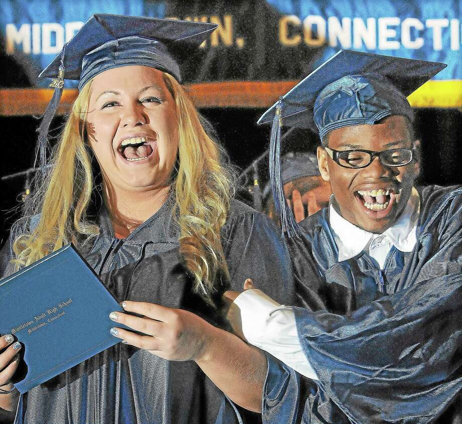 Middletown residents Vivian Brow and Royal Cade celebrate after receiving their diplomas at the 2013 commencement ceremony at Middletown High School. Photo: File Photo  / TheMiddletownPress