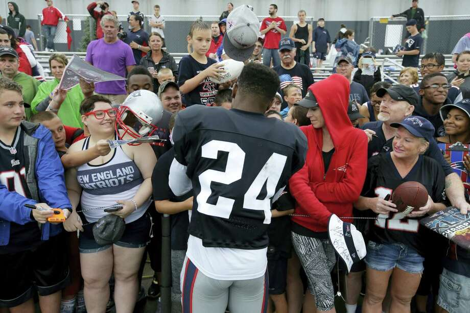 New England Patriots cornerback Cyrus Jones (24) signs autographs for fans following training camp practice Sunday in Foxborough, Mass. Photo: The Associated Press  / AP