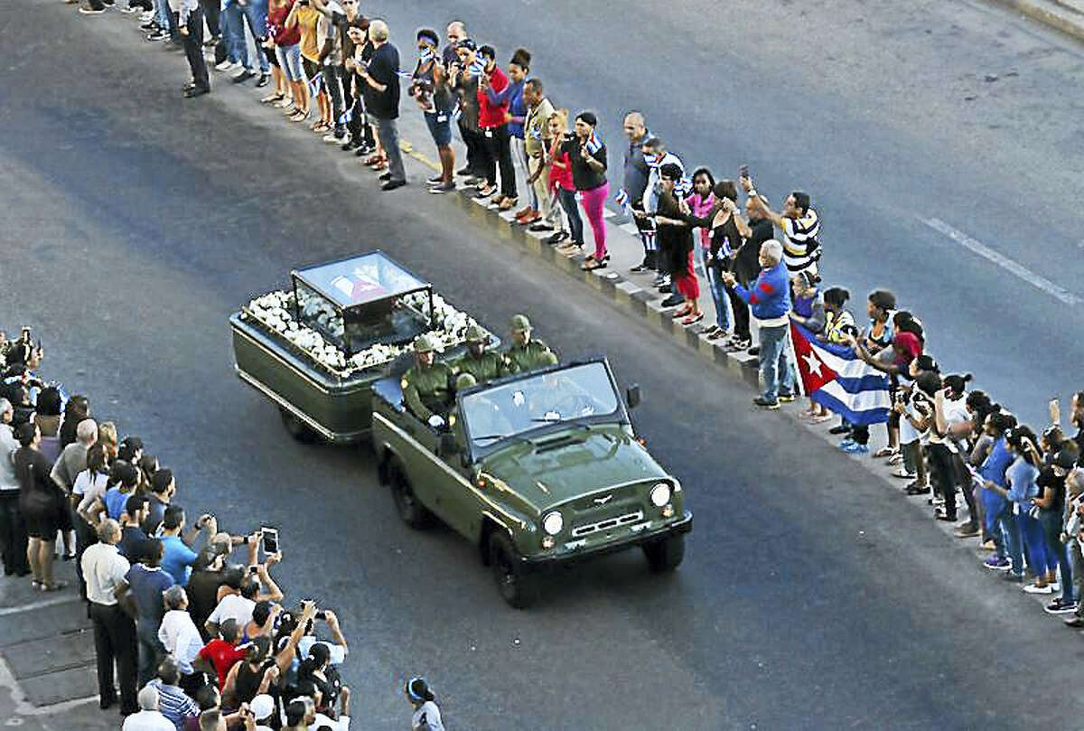 Flag-covered coffin containing Castro's ashes is displayed in a glass case on a flower-filled trailer pulled by a Jeep through the streets of Havana.