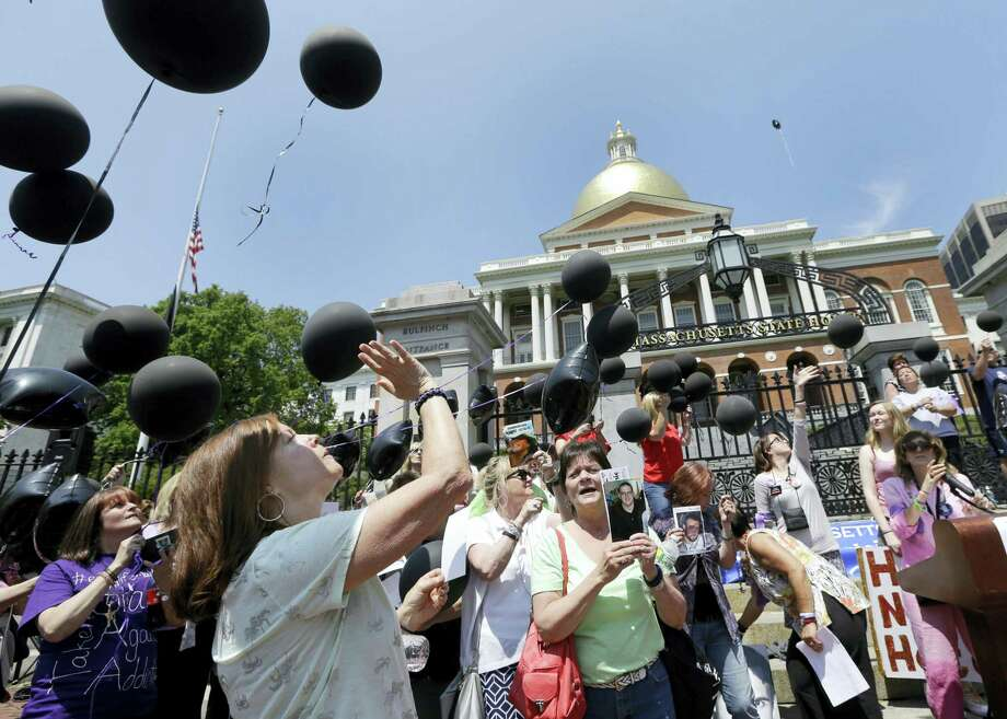 Deborah Lehti, left, of Abington, Mass. gestures after releasing a black balloon in remembrance of her son, Kai, who died of a drug overdose, during a Rally to Face Addiction at the Statehouse, Wednesday, May 25, 2016, in Boston. Photo: AP Photo/Elise Amendola   / Copyright 2016 The Associated Press. All rights reserved. This material may not be published, broadcast, rewritten or redistribu