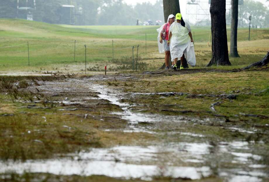 Women walk by the 18th hole after third round play was suspended for the day at the PGA Championship at Baltusrol Golf Club in Springfield, N.J., Saturday. Photo: Tony Gutierrez — The Associated Press  / Copyright 2016 The Associated Press. All rights reserved. This material may not be published, broadcast, rewritten or redistribu