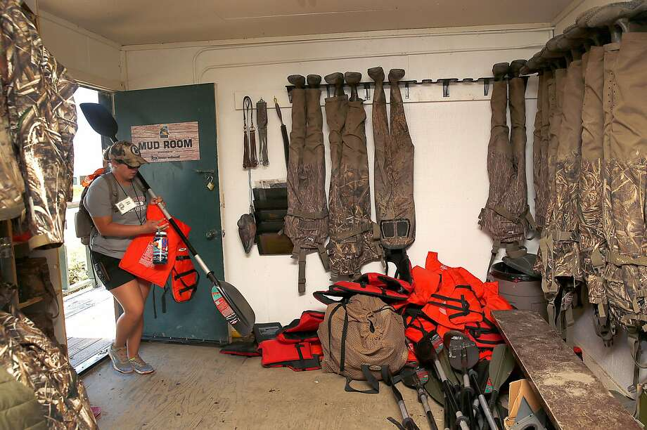 Kayak guide Taylor Byars brings paddles and life jackets to the mud room at Grizzly Ranch on the Suisun Marsh on Wednesday, July 26, 2017, in Suisun City, Calif.   30 youth from inner cities in the Bay Area are taking part in an outdoors camp Photo: Liz Hafalia, The Chronicle