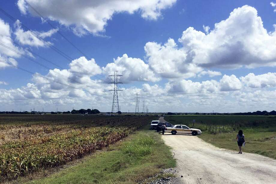 Police cars block access to the site where a hot air balloon crashed early Saturday, July 30, 2016, near Lockhart, Texas.  At least 16 people were on board the balloon, which Federal Aviation Administration spokesman Lynn Lunsford said caught fire before crashing into a pasture shortly after 7:40 a.m. Saturday near Lockhart. No one appeared to survive the crash, authorities said. Photo: AP Photo/James Vertuno   / AP
