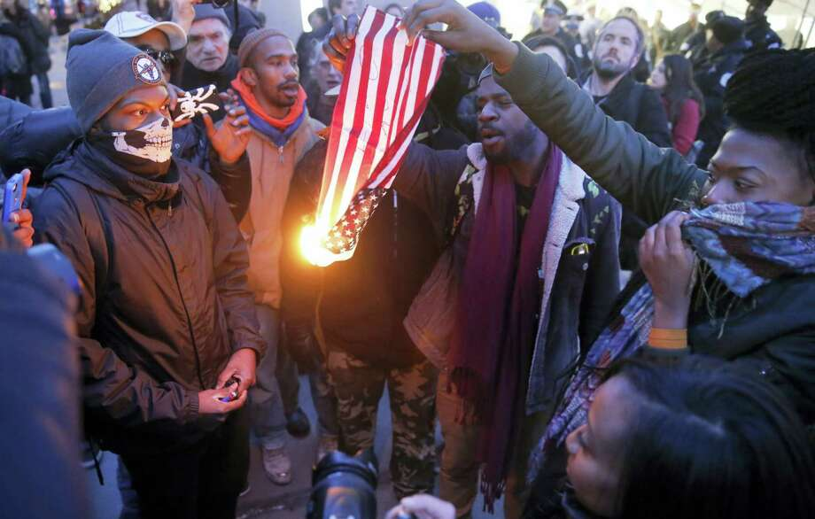 "In this Feb. 23, 2016, file photo, protesters burn an American flag in Chicago. Champaign County Ill., State's Attorney Julia Rietz was alerted on July 4, 2016, that police had just arrested a resident on suspicion of burning an American flag. Rietz said she knew ""immediately"" that the Urbana Police Department needed to release him. The state law used to jail him, though clear in its prohibition of desecrating either the U.S. or state flags, is unconstitutional. Photo: AP Photo/Charles Rex Arbogast, File   / Copyright 2016 The Associated Press. All rights reserved. This material may not be published, broadcast, rewritten or redistribu"